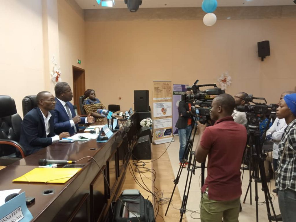 Picture of a press conference in Benin. Two men and one woman sitting at a table with cameras in front of them.