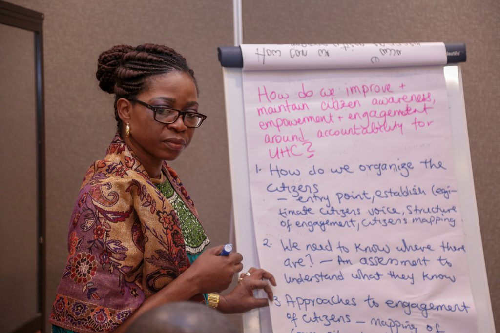 "Woman wearing glasses and a colorful outfit looking away from the camera as she holds a marker and has a flipchart with the following written on it: ""How do we improve + maintain citizen awareness, empowerment + engagement around accountability for UHC? 1. How do we organize the citizens? Entry point, establish citizens voice, structure of engagement, citizen mapping. 2. We need to know where they are? An assessment to understand what they know. 3.Approaches to engagement of citizens – mapping of…"