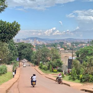 Picture of a road with people walking and riding on motorbikes that leads into Kampala, Uganda on a sunny day.