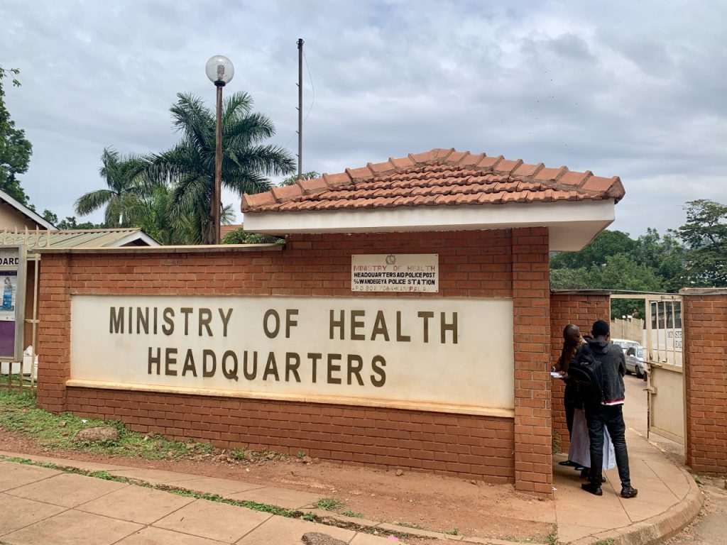 Picture of the Ministry of Health sign in front of the building in Kampala, Uganda. Sign color is beige and is bordered with brick.