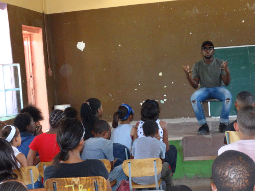 A man teaches in front of a classroom of young students